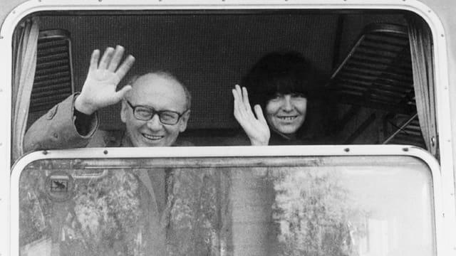 Ernst Jandl und Friederike Mayröcker blicken lachend aus einem geöffneten Zugfenster und winken.