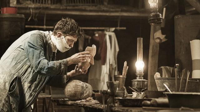 Ein Mann in einer Werkstatt. Er hält eine Maske in der Hand.