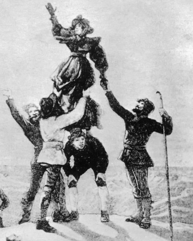 Eine Alpinistin und vier Männer auf einem Berggipfel.