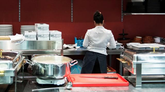 Ein Frau arbeitet in einer Hotelküche.