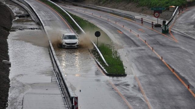 Auto fährt über eine überschwemmte Autobahn.
