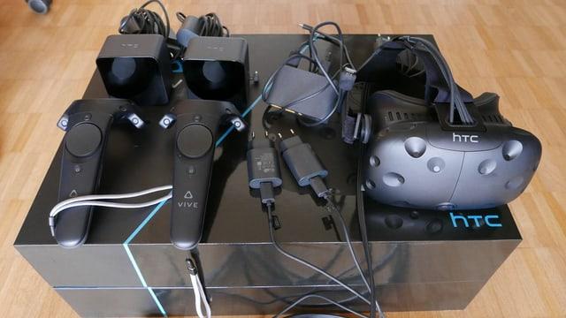 Eine Brille, zwei Sensoren, zwei Controller und einiges an Kabeln kommt aus der HTC Vive Box.