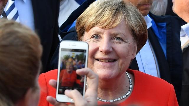 Angela Merkel sa lascha fotografar a chaschun d'ina visita tar in project d'agid a Berlin.