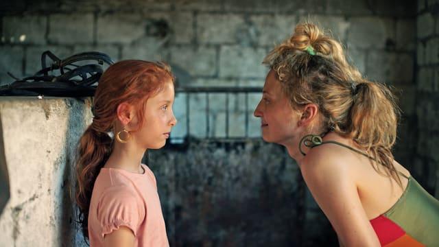 Ein Mädchen und eine Frau stehen sich gegenüber und schauen sich ins Gesicht.