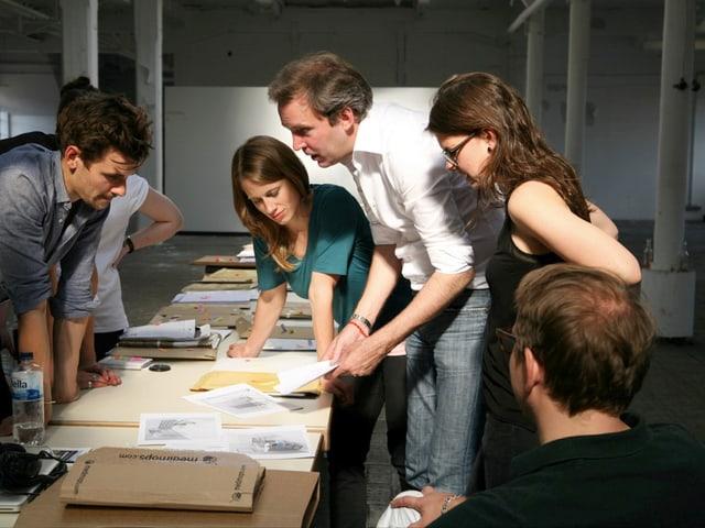 Tilman Kriesel steht mit anderen Leuten um einen Tisch herum