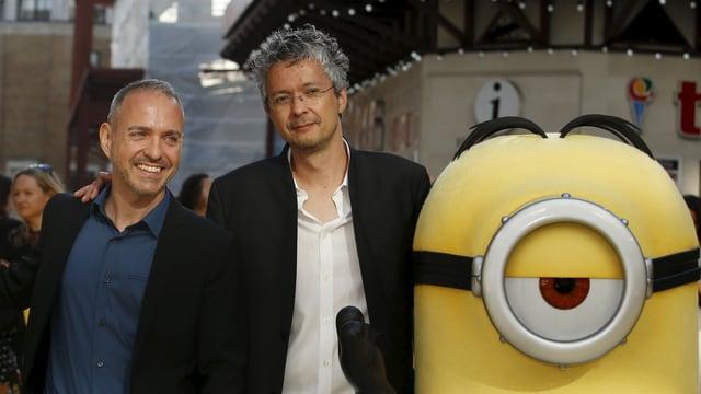 Das Regie-Duo Kyle Balda & Pierre Coffin posieren auf der Premiere mit einem Minion.