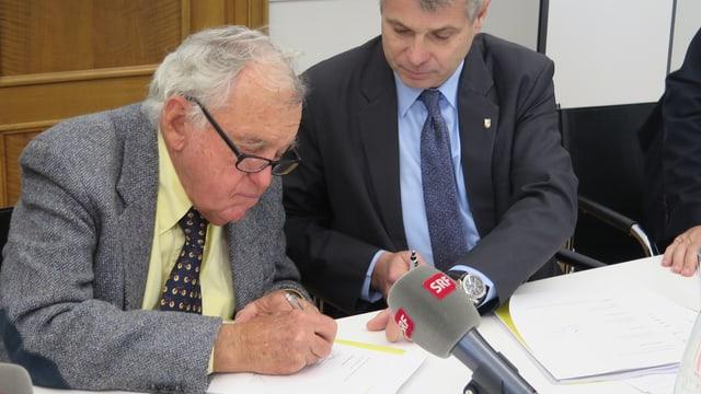 Mann unterschreibt ein Papier