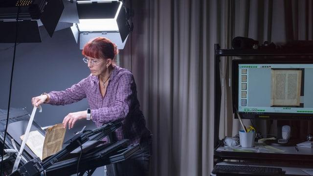 Eine Frau scannt einen alten Druck ein.