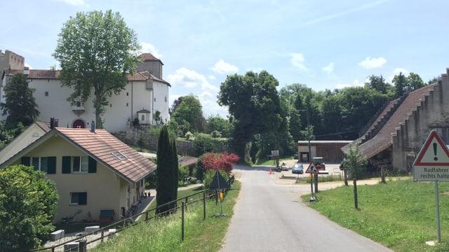 Strasse, links und rechts Wiese, ein Schloss, ein Bauernhof