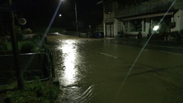 Überflutete Strasse im nächtlichen Wattenwil.