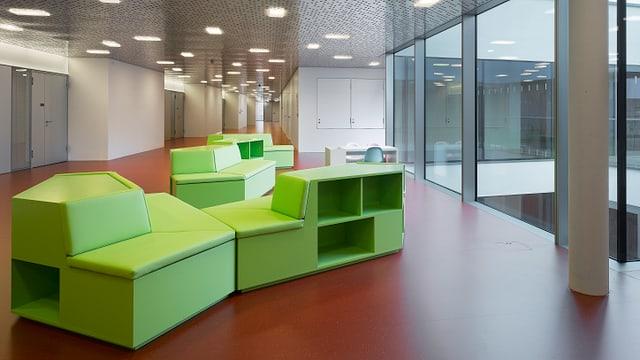 Gang im UKBB mit grasgrünen Sitzmöbeln.