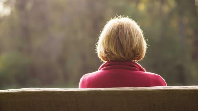Eine Frau mit rotem Mantel auf einer Bank.