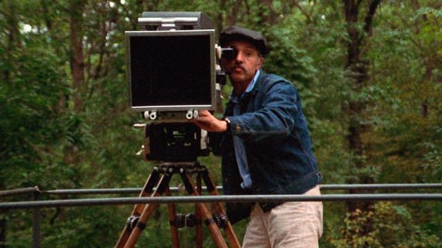 Mann im Wald mit Kamera in Richtung Zuschauer.