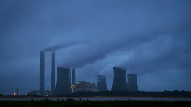 Symbolbild: Stark rauchnenden Kraftwerk in der Ferne.