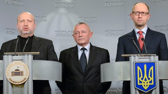 Drei Männer sprechen vor den Medien.