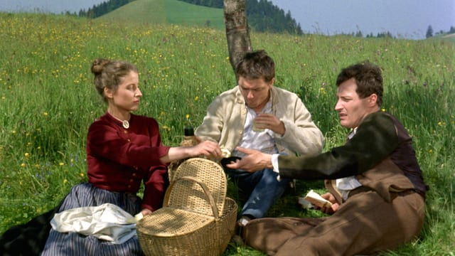 Zwei Männer und eine Frau beim Picknick. In der Mitte steht ein Picknickkorb. Die Frau reicht einem der Männer ein Sandwich.