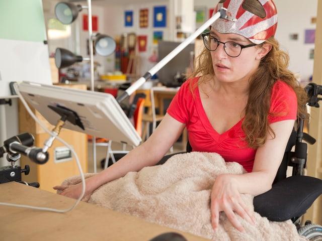 Eine Bewohnerin des Kulturparks mit einer Art Helm, mit dem sie den Computer bedient.