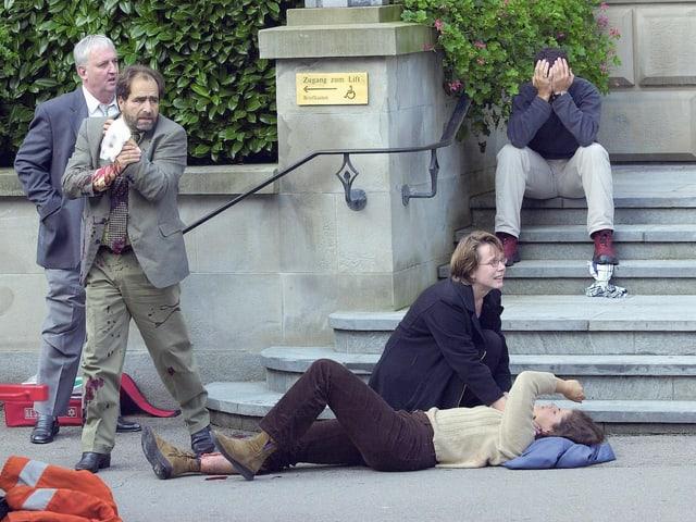 verletzte Person liegt am Boden, Parlamentarier verlässt in blutiger Kleidung das Gebäude.