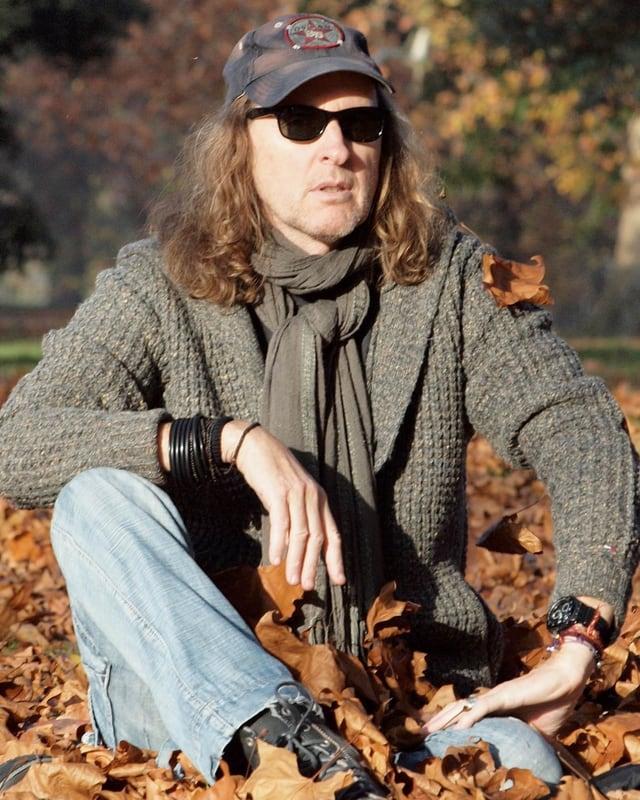 Chris von Rohr sitzt im Laub