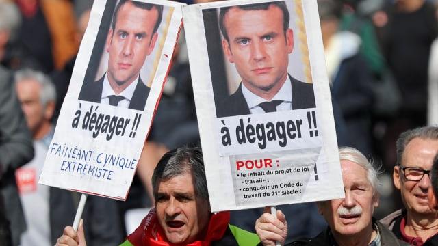 Protestierende halten Schilder mit dem Bild Macrons hoch, die Aufforderung, die Revision zurückzuziehen.