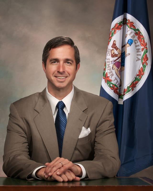 Gordon Stettinius als Gouverneur. Er trägt einen grauen Anzug.