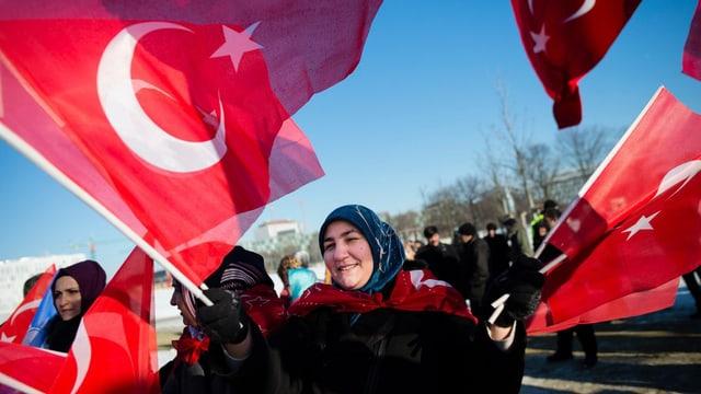 Eine Frau schwenkt mehrere türkische Fahnen.