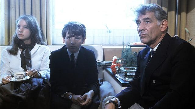 Leonard Bernstein und seine zwei Kindern sitzen auf Sofas.