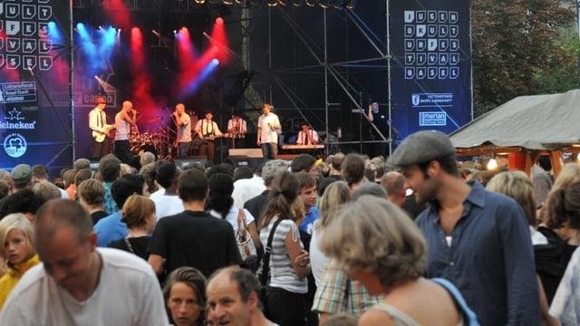 Im Hintergrund eine mit Spots beleuchtete Bühne, vorne dran vor allem junge Menschen