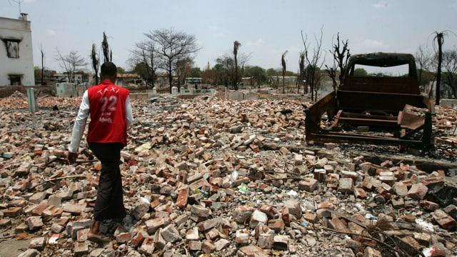 Ein Mann geht auf einem Trümmerfeld an einem verkohlten Auto vorbei.