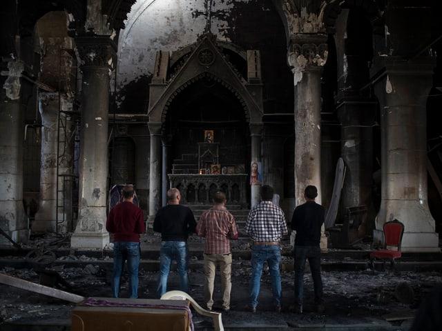 Menschen betrachten die zerstörte Kirche in Karakosch.