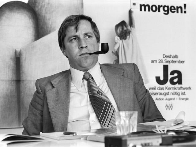 Ein junger Blocher aus dem Jahre 1980 mit Pfeife und Krawatte. Er blickt misstrauisch in die Ferne, schwarz-weiss-Bild