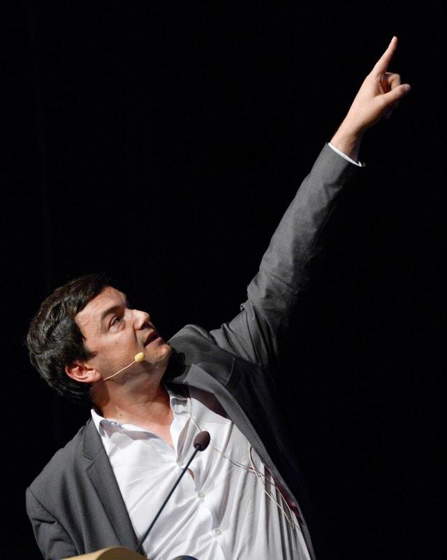 Piketty bei einem Vortrag, zeigt mit ausgestrecktem Arm auf einen Punkt auf einer nicht sichtbaren Leinwand