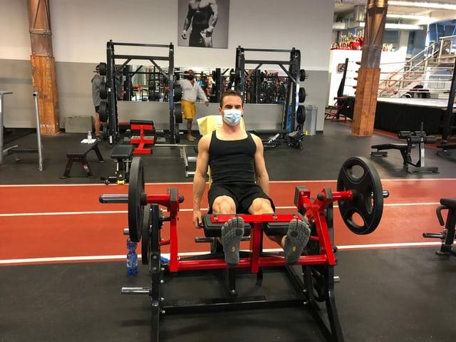 Mann trainiert mit Maske an Fitnessgerät