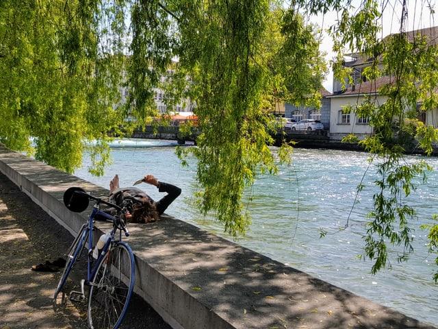 Eine Frau liegt am Ufer der Aare im Schatten. Sie liest ein Buch.