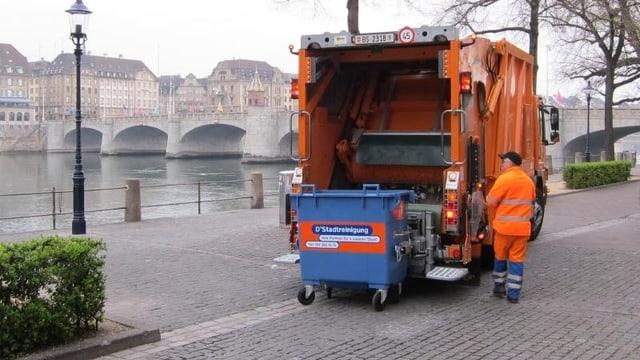 Am Basler Rheinufer wird ein blauer Abfallcontainer von der Basler Stadtreinigung entleert.