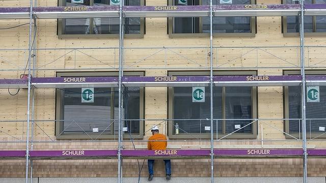 Ein Bauarbeiter sitzt auf einem Baugerüst.