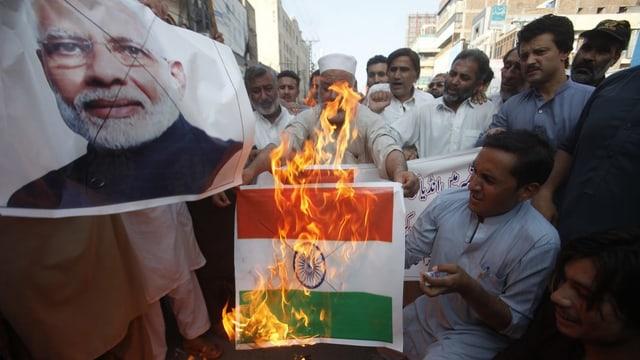 Menschen verbrennen Indienflagge.