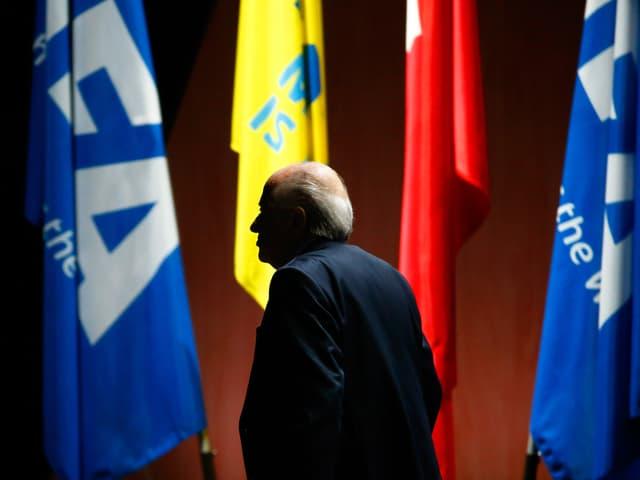 Hinteransicht von Fifa-Präsident Sepp Blatter, der vor Fahnen steht.