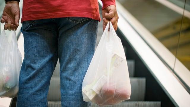 Eine Person hält gefüllte weisse Plastiksäcke in der Hand.