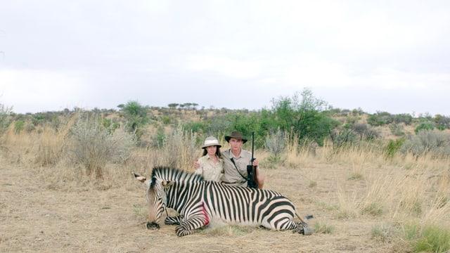 In Afrika: Ein Jägerpaar posiert hinter einem toten Zebra.