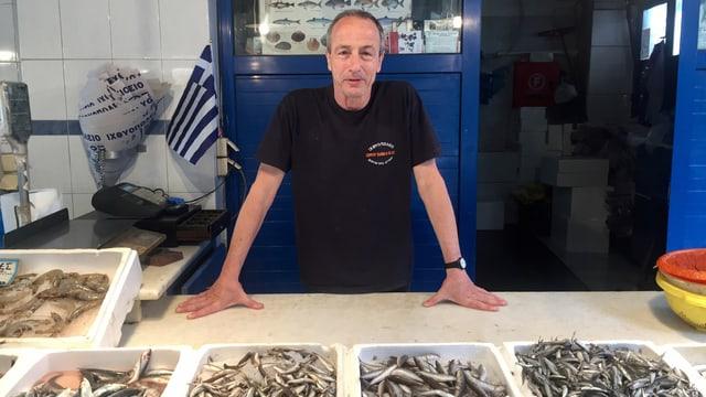 Mann vor Kisten mit kleinen Fischen drin in einem Laden.