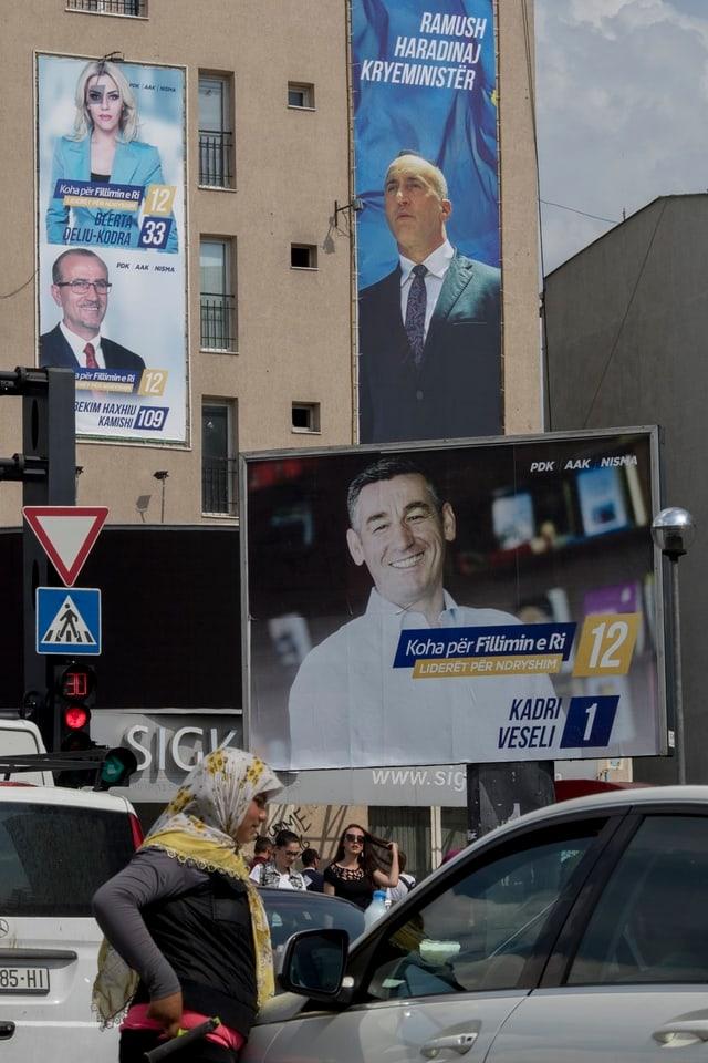 Eine Frau mit Kopftuch an einem Auto, im Hintergrund Wahlplakate.