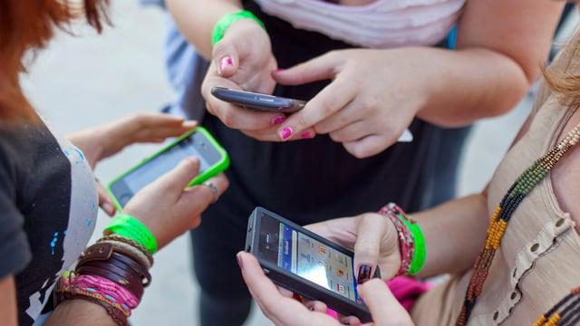 Drei junge Frauen stehen im Kreis, jede hält ein Smartphone in der Hand.