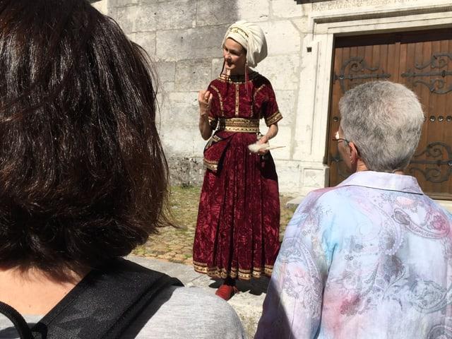 Stadtführerin trägt rotes Kostüm mit weisser Haube.