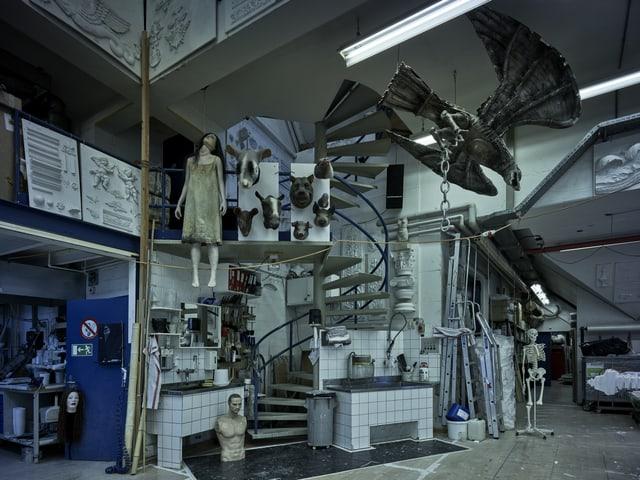 Ein voller, düsterer Raum mit einer erhängten Schaufensterpuppe, Skeletten, Torsos.