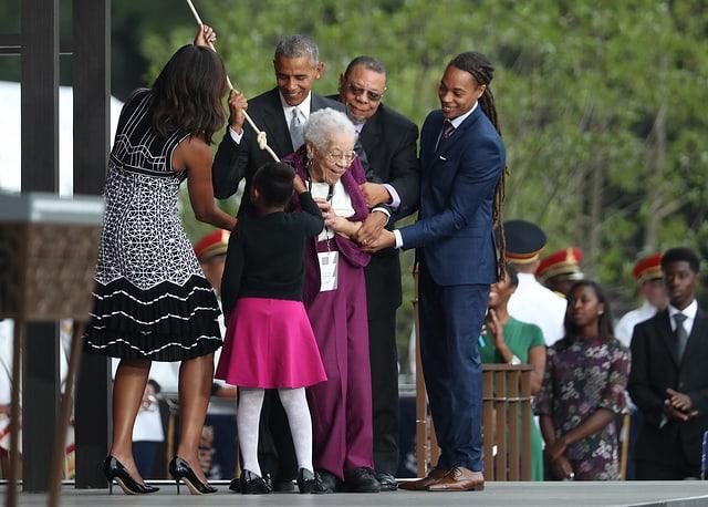 Ruth Bonner zieht an einer Schnur, daneben Barack Obama und weitere Menschen