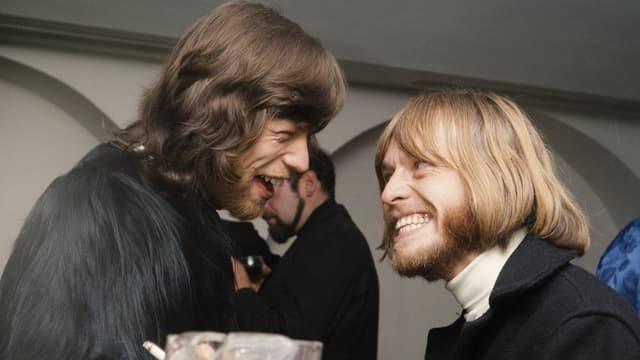 Zwei Männer mit längeren Haaren und Bärten. Jagger trägt einen Mantel mit langem Fell.