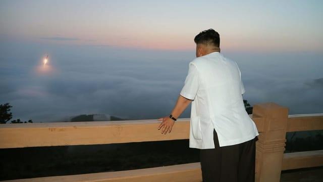 Kim Jong Un schaut zu, wie eine Rakete in den Himmel steigt.