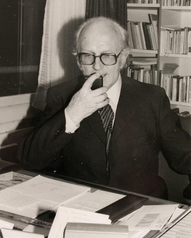 Mann mit Glatze, Brille und im Anzug sitzt an einem Schreibtisch neben dem Fenster und spricht in eine Diktaphon.