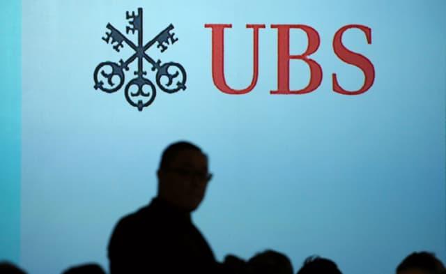 Symbolbild: UBS-Logo an der Wand, davor Personensilhouetten.